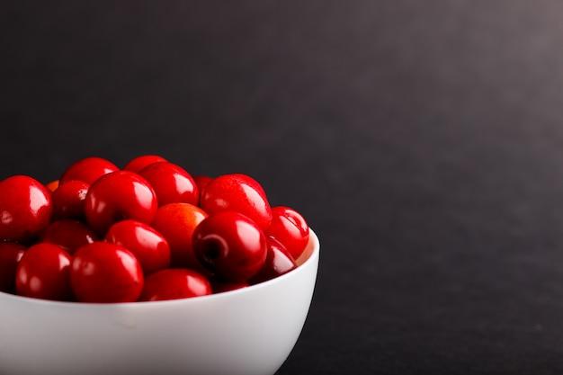 黒い背景に白いボウルに新鮮な赤い甘いチェリー