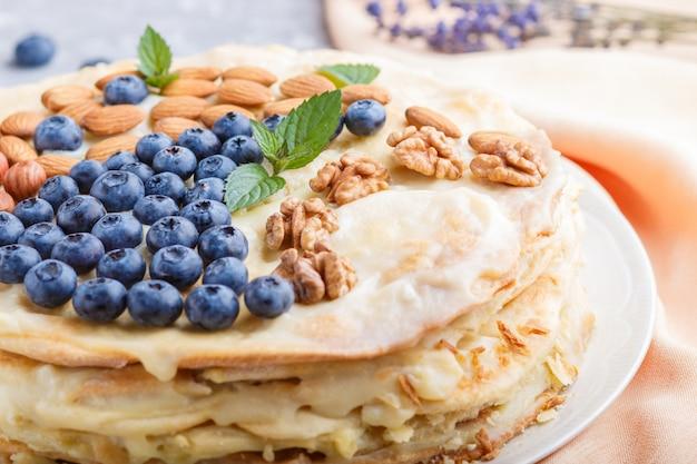 Домашний слоеный пирог наполеона с молочным кремом украшенный черникой миндаль грецкие орехи фундук мята на сером бетонном фоне
