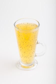 Стакан мандаринового напитка оранжевого цвета с семенами базилика на белом фоне
