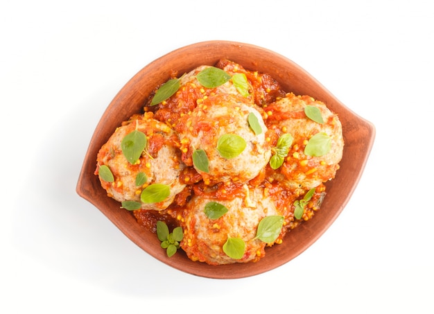 トマトソースオレガノと豚肉ミートボールは、白い背景で隔離の粘土ボウルにスパイスとハーブを残します