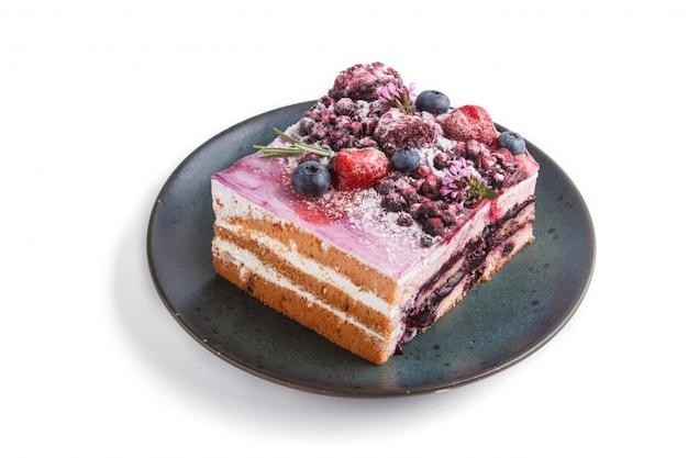 Ягодный пирог с молочным кремом и черничным вареньем на синей керамической тарелке на белом фоне