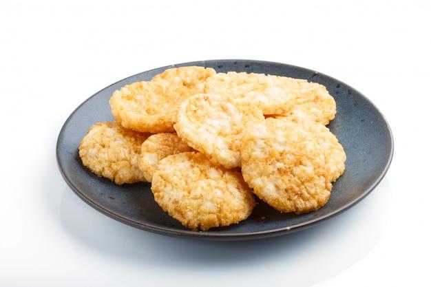 白い背景に分離された青いセラミックプレートに蜂蜜と醤油と伝統的な日本の米チップクッキー