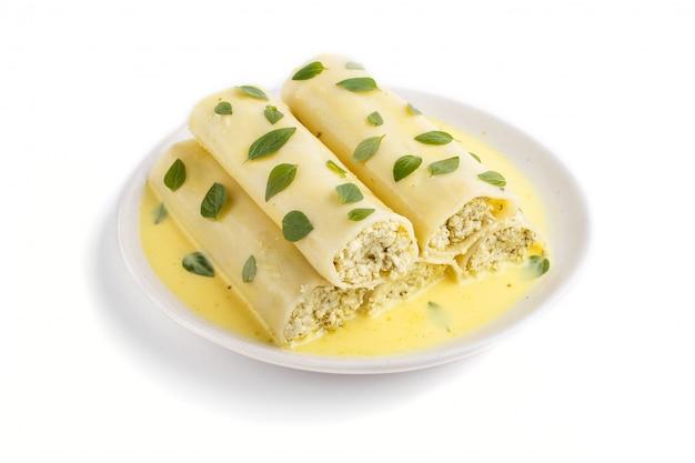 卵ソースクリームチーズとオレガノの葉の白い背景で隔離のカネロニパスタ
