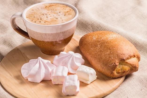 甘いパン、メレンゲ、木の板の上にコーヒーカップ