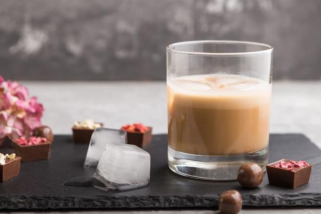ガラスと黒い石のスレート板に氷を入れた甘いチョコレートリキュール。側面図