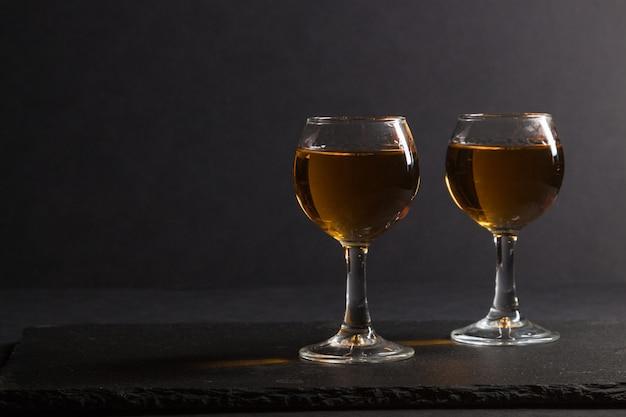黒い石のスレートボード上のウイスキーのグラス。側面図