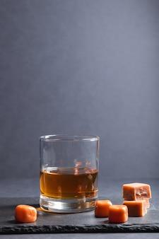 黒い石のスレート板にキャラメルキャンディーとウイスキーのグラス。側面図
