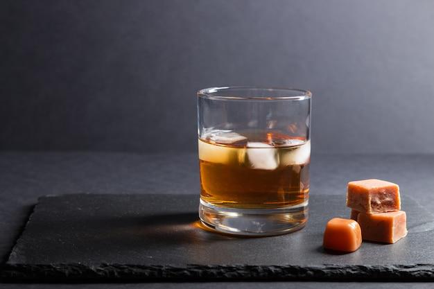 黒い石のスレート板に氷とキャラメルのお菓子を添えたウイスキーのグラス。側面図