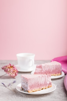 Домашний розовый чизкейк с чашкой кофе. вид сбоку