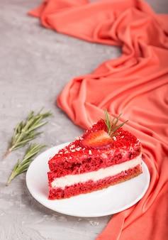 Домашний красный бархатный торт с молочным кремом и клубникой на серой бетонной поверхности. вид сбоку, выборочный фокус.