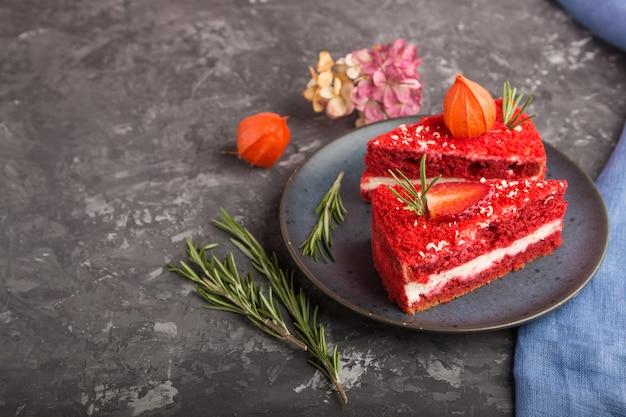 Домашний красный бархатный торт с молочным кремом и клубникой на черной бетонной поверхности. вид сбоку, копия пространства.