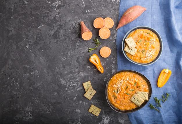 サツマイモまたはバタタのクリームスープ、ゴマと黒いコンクリートの表面にある青いセラミックボウルのスナック。トップビュー、コピースペース。