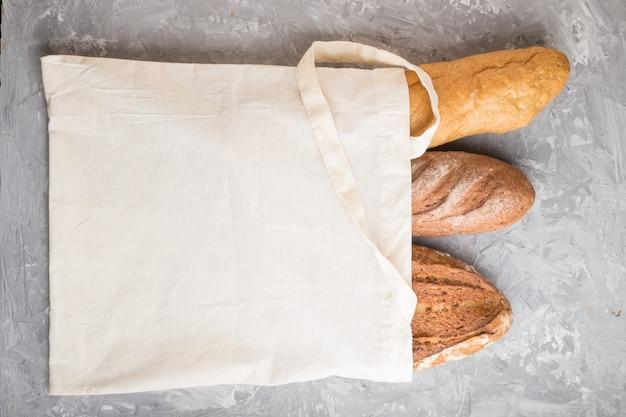 灰色のコンクリート背景に焼きたてのパンと再利用可能な繊維食料品袋。トップビュー、コピースペース。