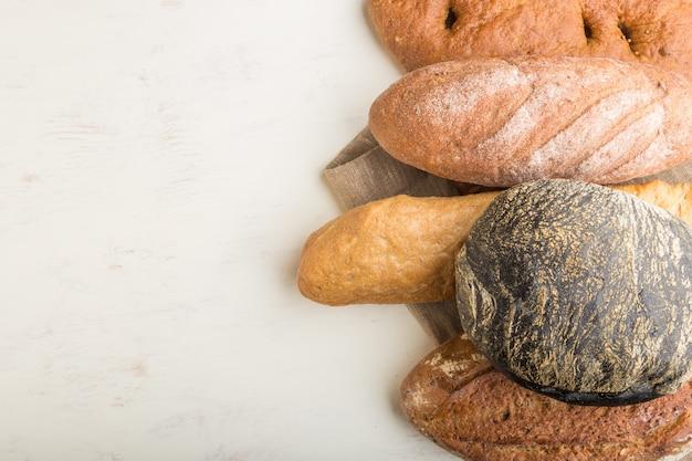 白い木製の背景に焼きたてのパンの種類。トップビュー、コピースペース。