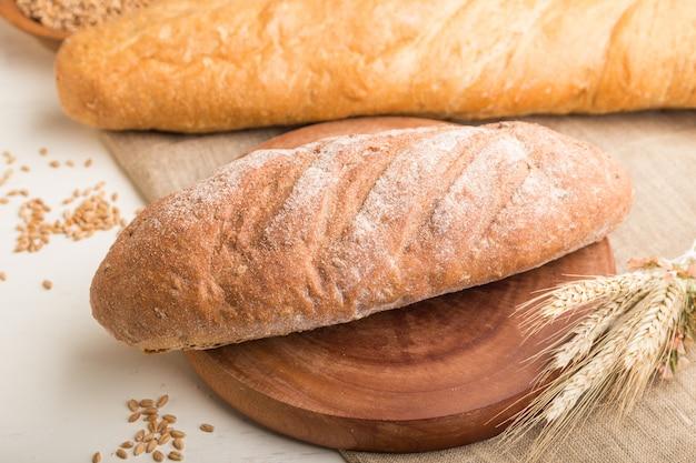 白い木製の壁に焼きたてのパンの種類。側面図、セレクティブフォーカス。