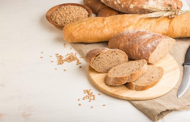 白い木製の壁に焼きたてのパンの種類とパンをスライスしました。側面図、コピースペース。