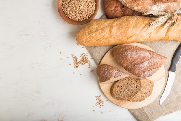 白い木製の背景に焼きたてのパンの種類とパンをスライスしました。トップビュー、コピースペース。