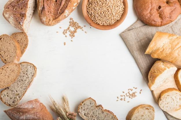 白い木製の壁にフレームの形で焼きたてのパンの種類。トップビュー、コピースペース。