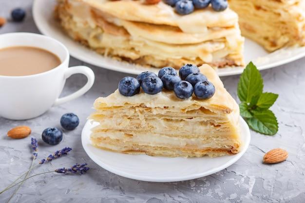 自家製の層状ナポレオンケーキとミルククリーム。グレーのコンクリート表面にブルーベリー、アーモンド、クルミ、ヘーゼルナッツ、ミントで飾られています。側面図、セレクティブフォーカス。