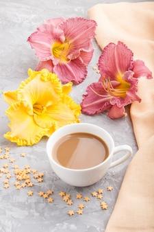 Желтая и фиолетовая чашка кофе лилий на серой бетонной поверхности, с оранжевой тканью. вид сбоку, крупным планом.