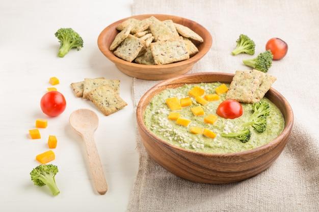 白い木製の表面に木製のボウルにクラッカーとチーズと緑のブロッコリークリームスープ。側面図。