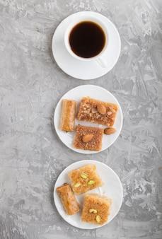白い皿に伝統的なアラビアのお菓子と灰色のコンクリート表面にコーヒーカップ。上面図。