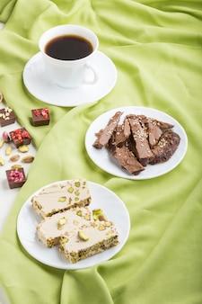 Традиционные арабские сладости, кунжутная халва с шоколадом и фисташкой и чашка кофе на зеленой текстильной поверхности. вид сбоку.
