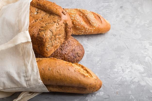 灰色のコンクリート背景に焼きたてのパンと再利用可能な食料品の袋。側面図、コピースペース。