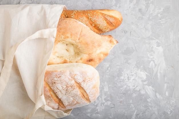 灰色のコンクリート背景に焼きたてのパンと再利用可能な食料品の袋。トップビュー、コピースペース。