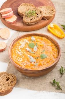 白い木製の表面に木製のボウルにゴマとサツマイモまたはバタタのクリームスープ。側面図、クローズアップ。