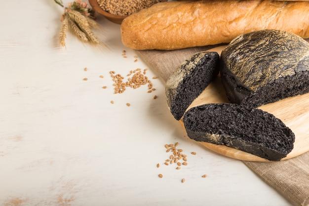 白い木製の背景に焼きたてのパンの種類と黒パンをスライスしました。側面図、コピースペース。