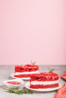 ミルククリームとストロベリーグレーとピンクの背景に自家製の赤いベルベットケーキ