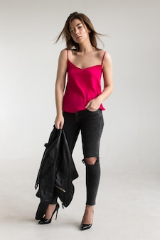 革のジャケットと紫のシャツの若い美しい茶色の髪の女性