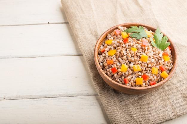 白い木製の背景に木製のボウルに野菜とそば米雑炊