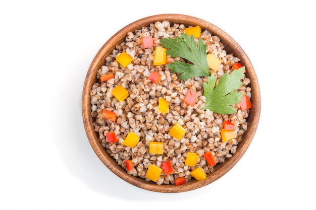 白い背景に分離された木製のボウルに野菜とそば米雑炊