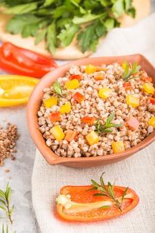 灰色のコンクリートの背景とリネンの繊維に粘土ボウルに野菜とそば米雑炊。側面図、クローズアップ、セレクティブフォーカス。