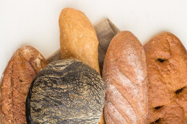 白い木製の背景に焼きたてのパンの種類。トップビュー、クローズアップ。