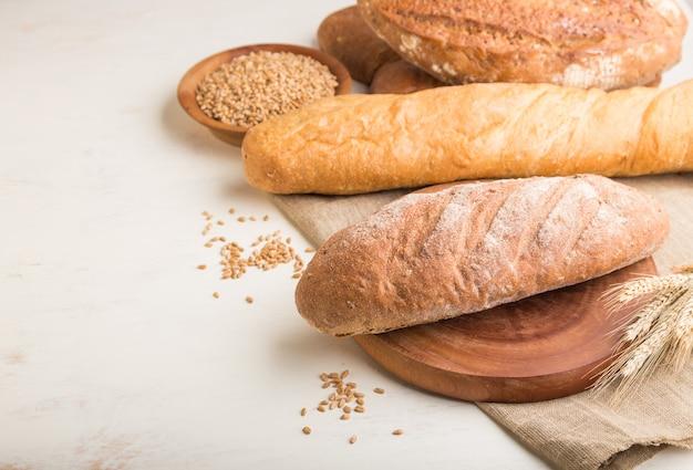 白い木製の背景に焼きたてのパンの種類。側面図、コピースペース。