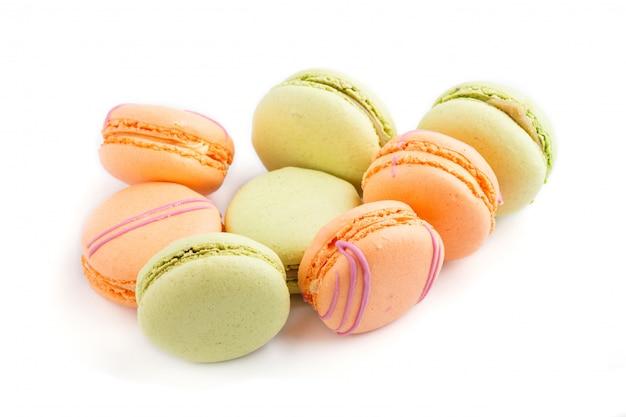 オレンジと緑のマカロンやマカロンのケーキが白い背景に、側面図に分離されました。