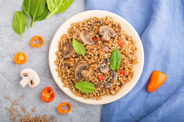スペルト小麦(ディンケル小麦)お粥と野菜とキノコの灰色のコンクリート背景にセラミックプレート。トップビュー、クローズアップ。