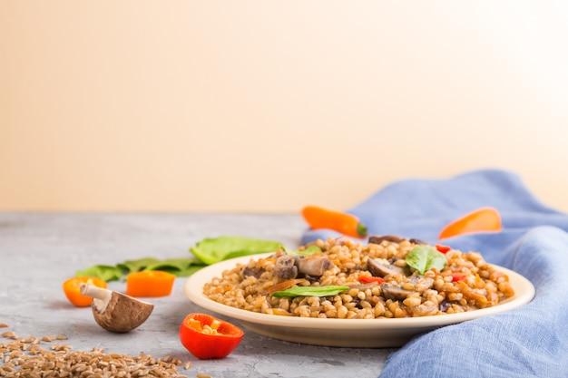 グレーとオレンジ色の背景にセラミックプレートにキノコと野菜とスペルト小麦(ディンケル小麦)お粥。側面図、セレクティブフォーカス、コピースペース。