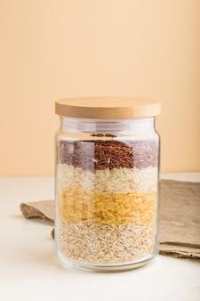Стеклянная банка с различными видами риса выливают в слои на белом и оранжевом фоне. вид сбоку, крупным планом.