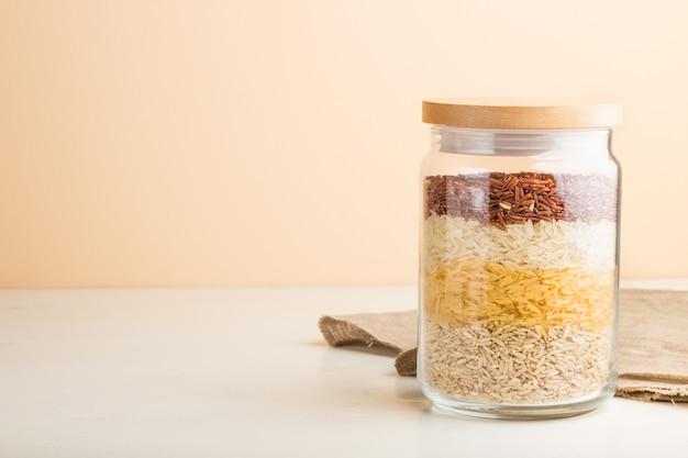 Стеклянная банка с различными видами риса выливают в слои на белом и оранжевом фоне. вид сбоку, копия пространства.