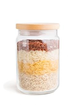 Стеклянная банка с различными видами риса выливают в слои, изолированные на белом фоне. вид сбоку.