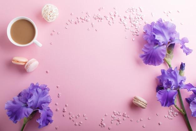 紫色のアイリスの花とピンクのパステル調の背景にコーヒーのカップ。