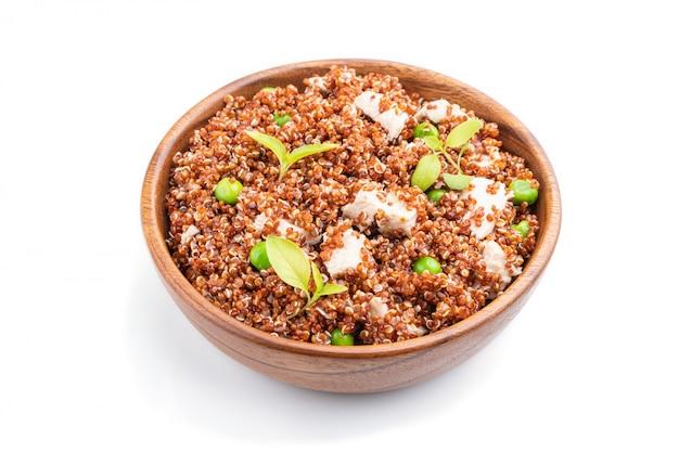 グリーンピースと白い背景に分離された木製のボウルにチキンとキノアのお粥。