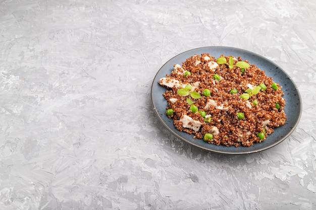グリーンピースと灰色のコンクリートの背景にセラミックプレートにチキンとキノアのお粥。