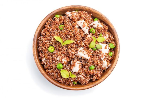 グリーンピースと白い背景に分離された木製のボウルにチキンとキノアのお粥。上面図。