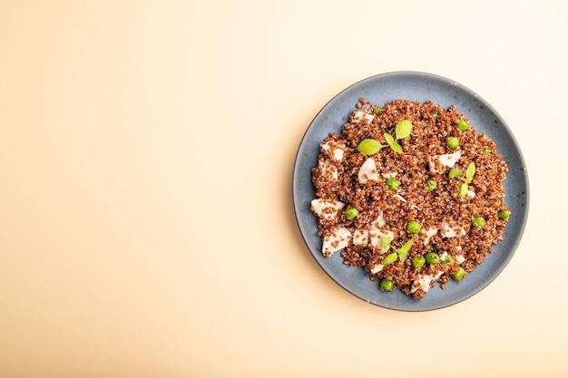 グリーンピースとパステルオレンジの背景にセラミックプレートにチキンとキノアのお粥。