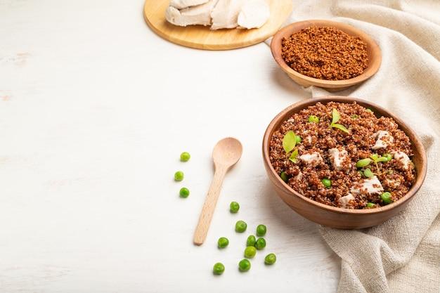 グリーンピースと白い木製の背景に木製のボウルにチキンとキノアのお粥。